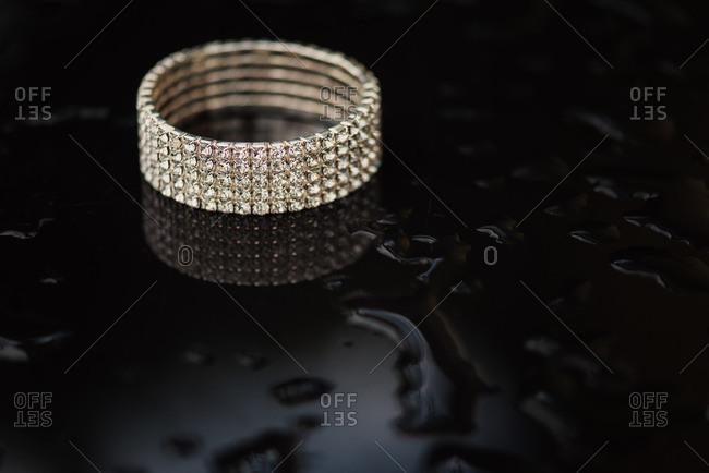 Diamond bracelet on black wet surface