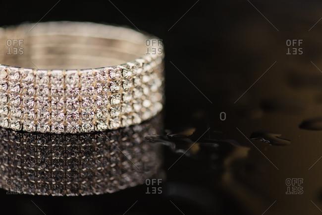 Close up of a diamond bracelet on black wet surface