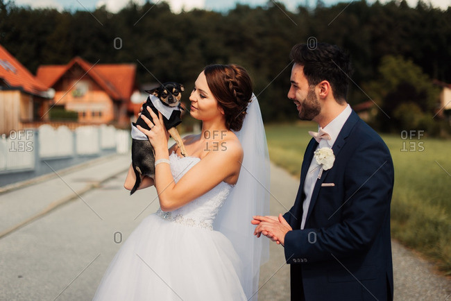 Bride holding a dog dressed in tuxedo outfit
