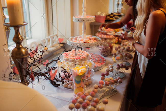 Guests picking treats on a dessert table at a wedding