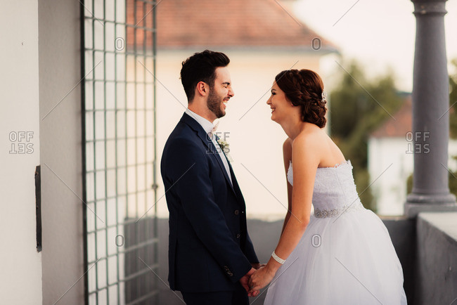 Bride and groom standing face to face laughing
