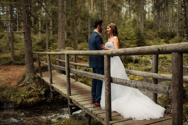 Newlywed couple standing face to face on a wooden bridge