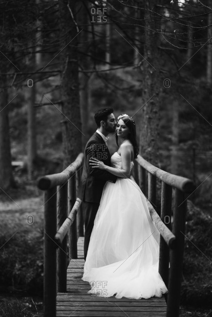Newlywed couple kissing on a wooden bridge in black and white
