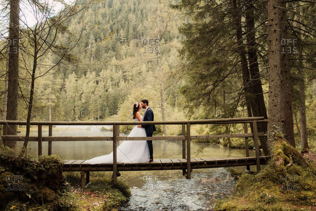 Bride and groom standing on a wooden bridge kissing