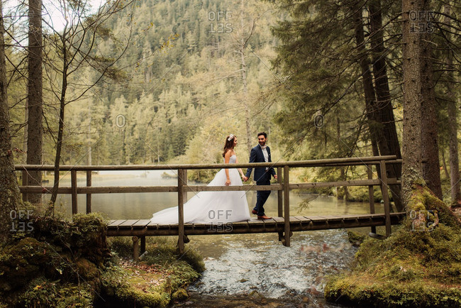 Bride and groom walking together on a wooden bridge