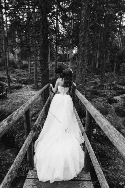 Bride and groom embraced on a wooden bridge in black and white