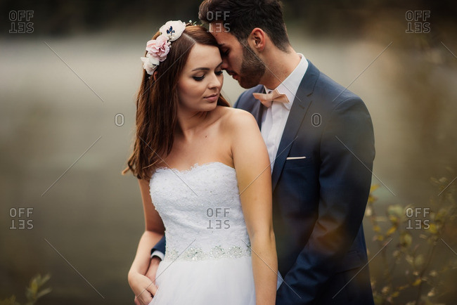 Loving bride and groom standing by a lake