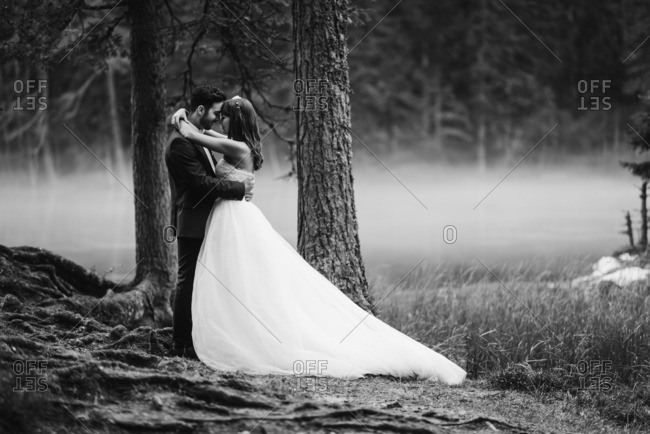 Bride and groom embraced by a foggy lake