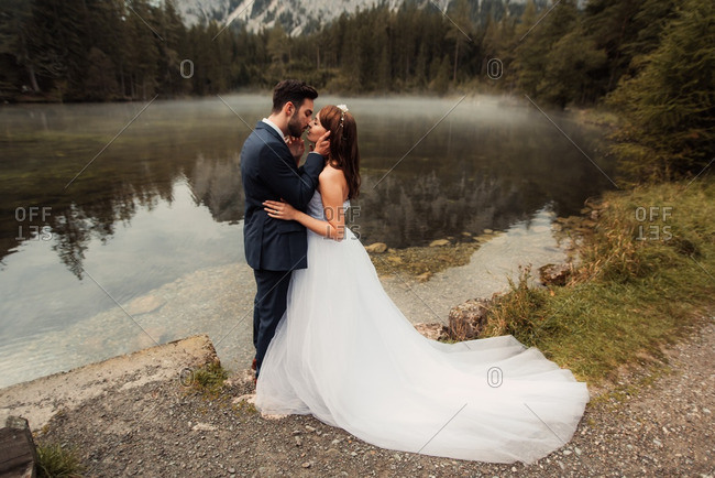 Groom kissing his bride by a foggy mountainside lake