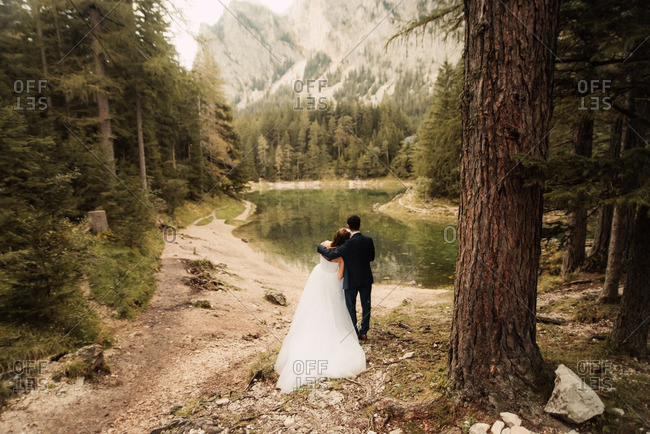 Bride resting head on her groom's shoulder by a mountainside lake