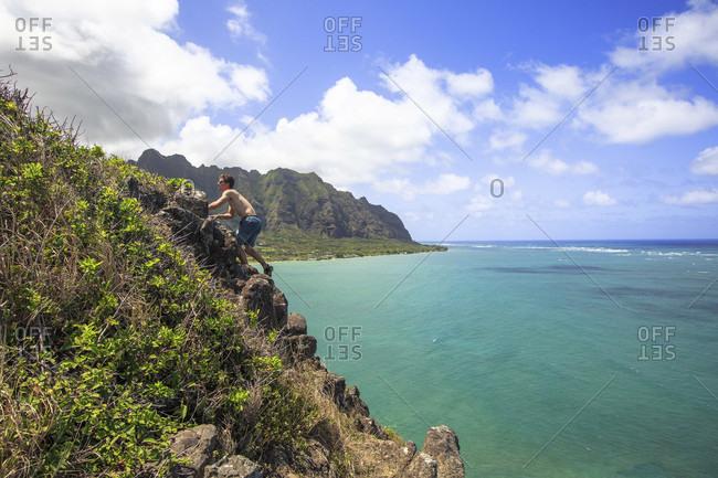 Oahu, Hawaii - April 18, 2015: Hiker climbs up Mokoli_i also know as chinaman's hat