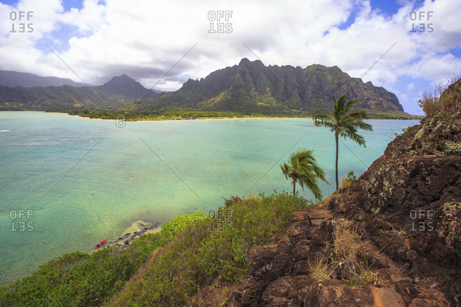 A kayak sits on the shores of Mokoli_i also knows as chinaman's hat, with Oahu, Hawaii in the distance