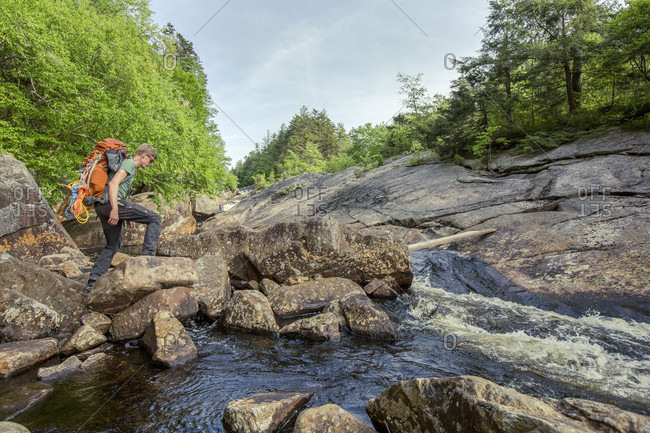 A rock climber crosses a stream in upstate New York