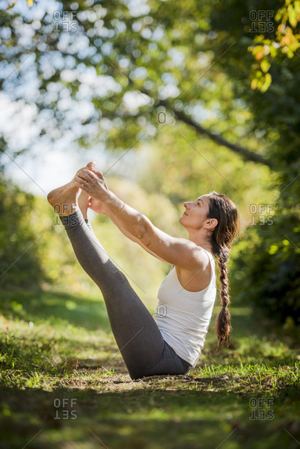 Woman practicing yoga on grassy landscape