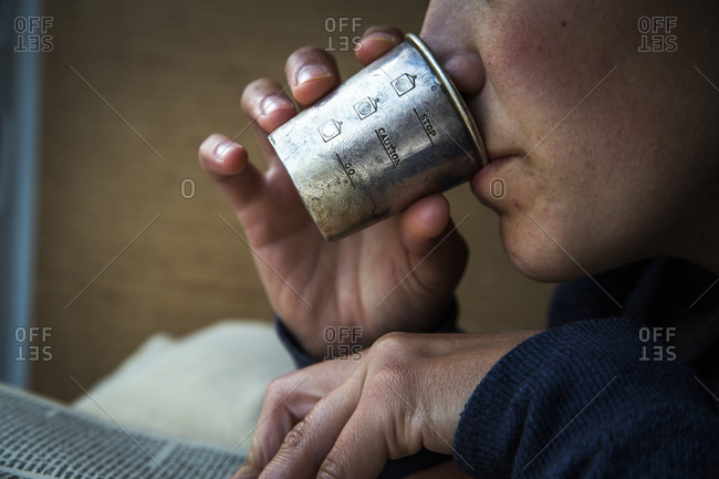 A woman reads a book and sips whiskey from a vintage steel cup, British Columbia