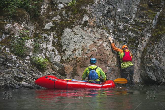 Man climbs a canyon wall accessed from a pack raft