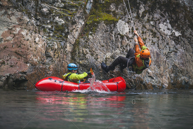 Man rappels off a cliff towards the Chehalis river and into a pack raft