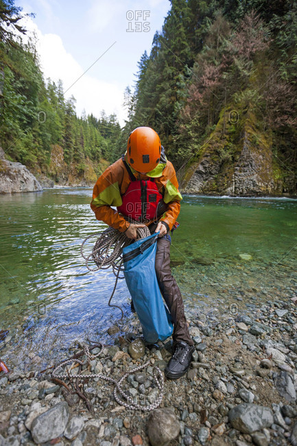 A climber stuffs a climbing rope into a dry bag during a pack rafting trip along the Chehalis river