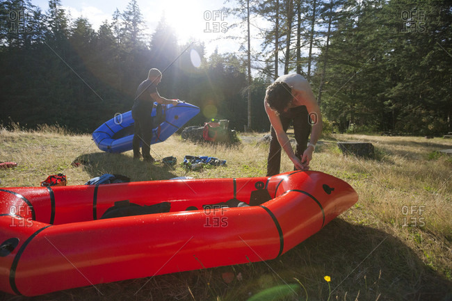 Two men deflating their rafts after a long day of pack rafting the Chehalis river, British Columbia, Canada