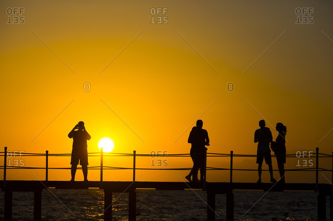Silhouette of tourist people exploring beach resort during sunset