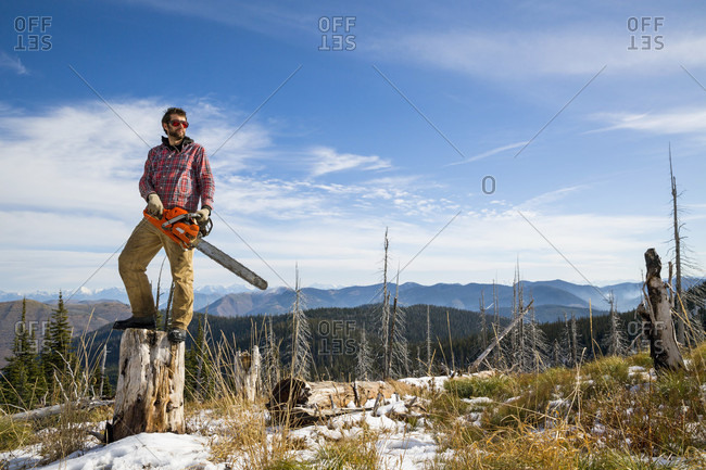 Man standing with chainsaw on tree stump while camping in Montana
