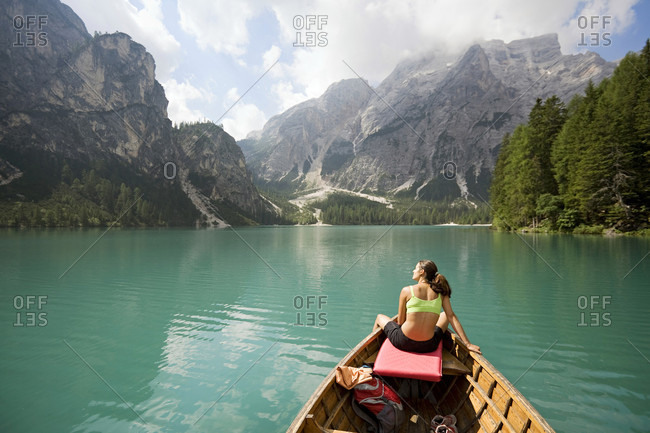 Young woman relaxing on the row of a boat on the lago di braies