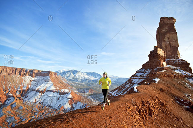 Female trail runner running beneath the Castleton tower in Utah