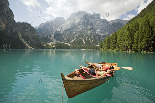 Man and woman relaxing in a boat on the lago di braies lake