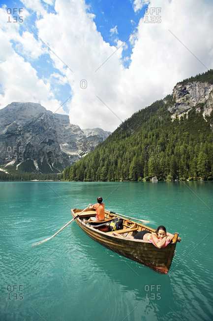 Man and woman riding on row boat in the lago di braies lake