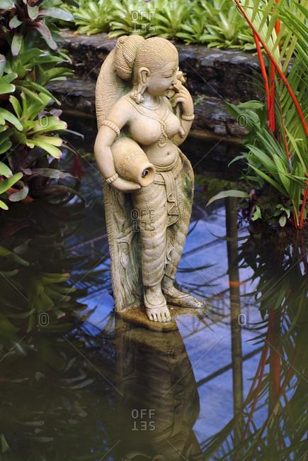 Thai statue of a female goddess in a garden koi pond, nong nooch, Thailand