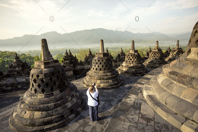 Woman taking pictures of stupas on Borobudur temple in Indonesia