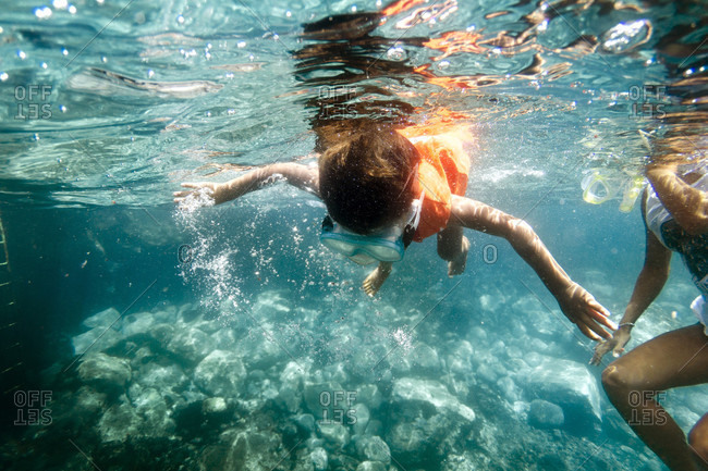 A boy snorkels with his mother in turquoise water