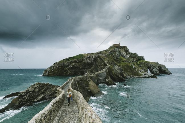 Tourist walking on the walkway to island of san juan de gaztelugatxe