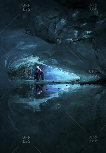 Person exploring glacier ice cave in Athabasca, Canada