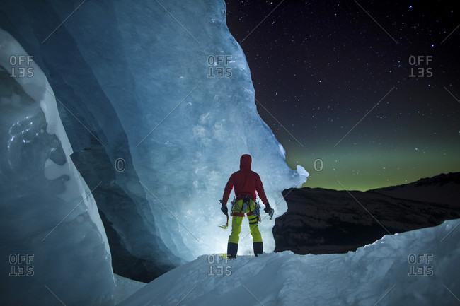 Ice climber standing at Athabasca glacier during aurora borealis
