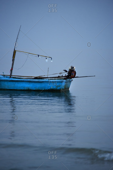 Blue fishing boat in the fog