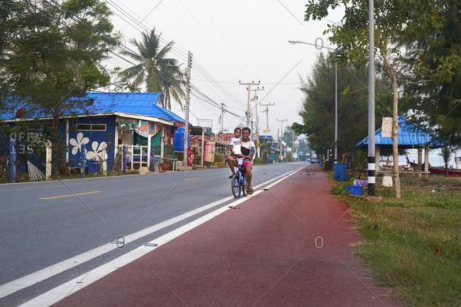 Sam Roi Yot, Thailand - 1/28/16: Man and his son on a bike