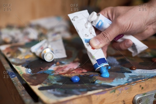 Process of creating art. Close-up view of male hand squeezing blue oil paint out of tube on messy palette