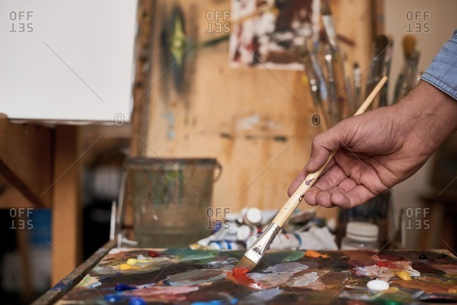 Artist working in studio. Male hand holding paintbrush and mixing oil paints on colorful messy palette, close-up view