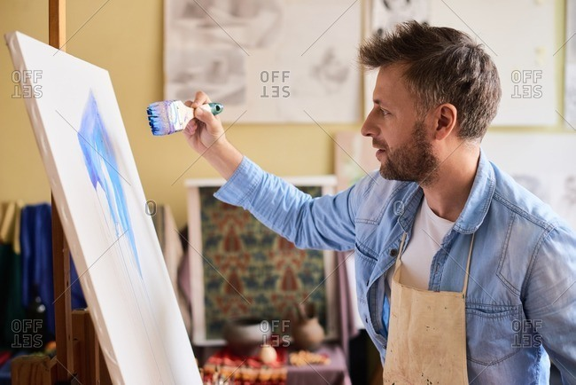 Creating abstract art. Middle-aged fair bearded artist in apron standing in front of easel and painting abstract picture with large paintbrush, side view