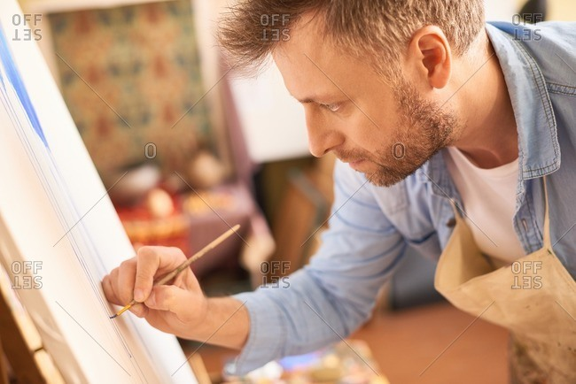 Inspired artist in studio. Concentrated bearded fair man in apron standing in front of easel and painting a picture with thin paintbrush