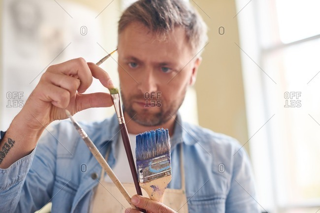 Getting ready for painting. Concentrated fair bearded artist holding paintbrushes of different sizes and checking its quality