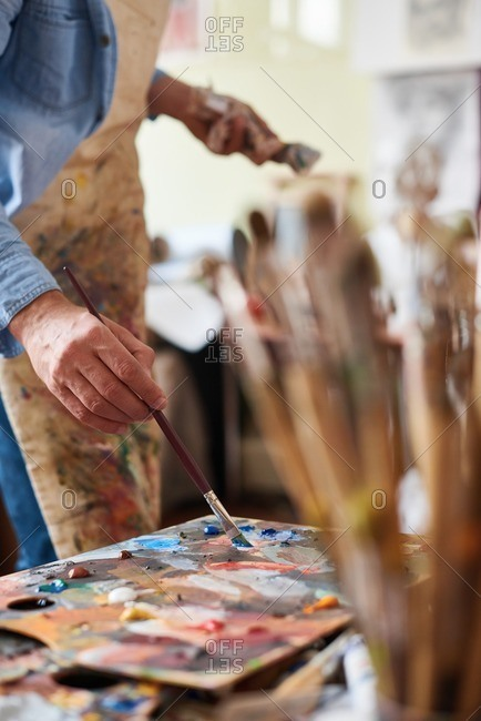Oil painting techniques. Close-up view of male artist in stained apron dipping paintbrush into oil paint on wooden multicolored palette