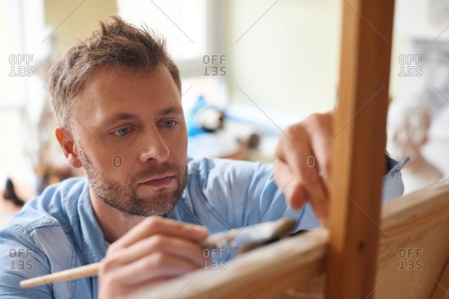 Enthusiastic artist at work. Concentrated middle-aged man standing in front of easel and practicing painting with paintbrush, close-up view