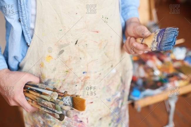 Getting ready for painting. Male artist in stained apron standing with different-size paintbrushes in his hands, close-up view