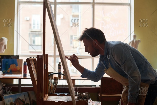 Improving painting skills. Concentrated middle-aged artist in apron standing in front of easel and painting with paintbrush on canvas paper, side view