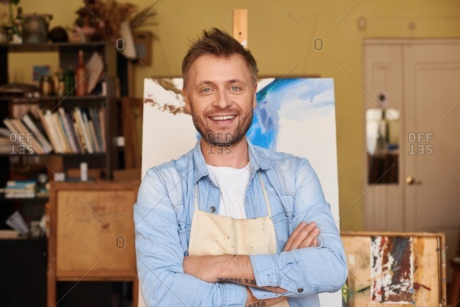 Successful art business. Waist-up portrait of middle-aged bearded painter standing against his creation with arms folded and smiling at camera happily