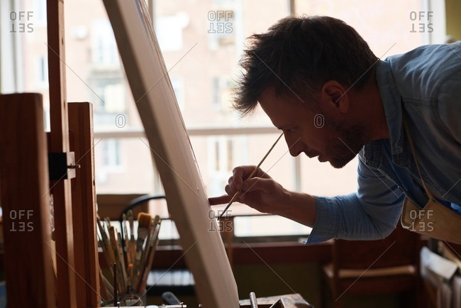 Enjoying art class. Close-up view of concentrated middle-aged man standing bent over easel and painting with paintbrush diligently