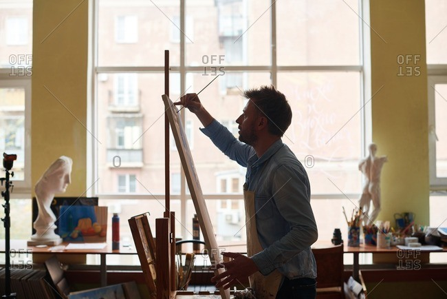 Having art class in studio. Enthusiastic middle-aged male student in apron finishing his acrylic painting using easel and paintbrush, side view