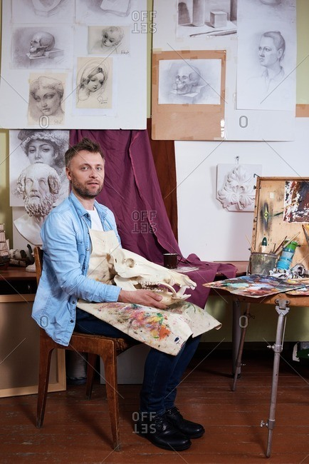 Surrounded by works of art. Portrait of middle-aged male artist in stained apron sitting with dinosaur skull in his art studio and looking at camera